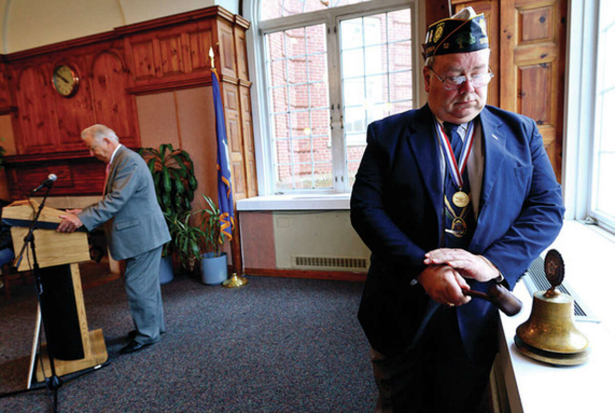 Past Commander of American Legion Post 12 Richard Olson rings a bell while mayor Richard Moccia reads the names of the Norwalk residents who died during the attack as part of the City of Norwalk Pearl Harbor Remebrance Day Friday at Norwalk City Hall. Hour photo / Erik Trautmann