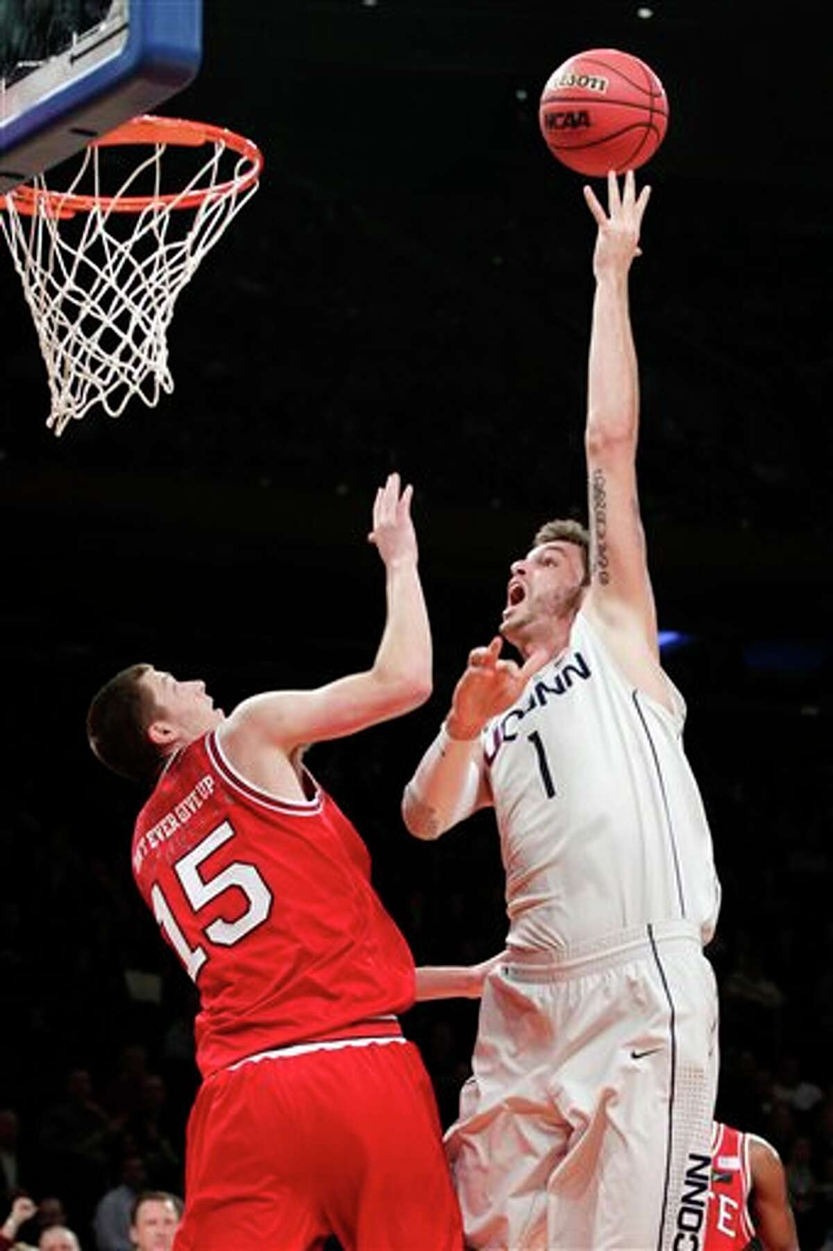 Connecticut's Enosch Wolf (1) shoots over North Carolina State's Scott Wood (15) during the first half of their NCAA college basketball game in the Jimmy V Classic at Madison Square Garden, Tuesday, Dec. 4, 2012, in New York. (AP Photo/Frank Franklin II)