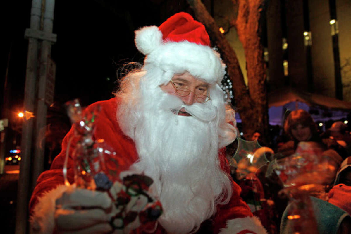 Santa gives bags of goodies to children at Norwalk City Hall's Holiday Tree Lighting Ceremony at 50 Washington Street in Norwalk Friday evening. Hour Photo / Danielle Robinson
