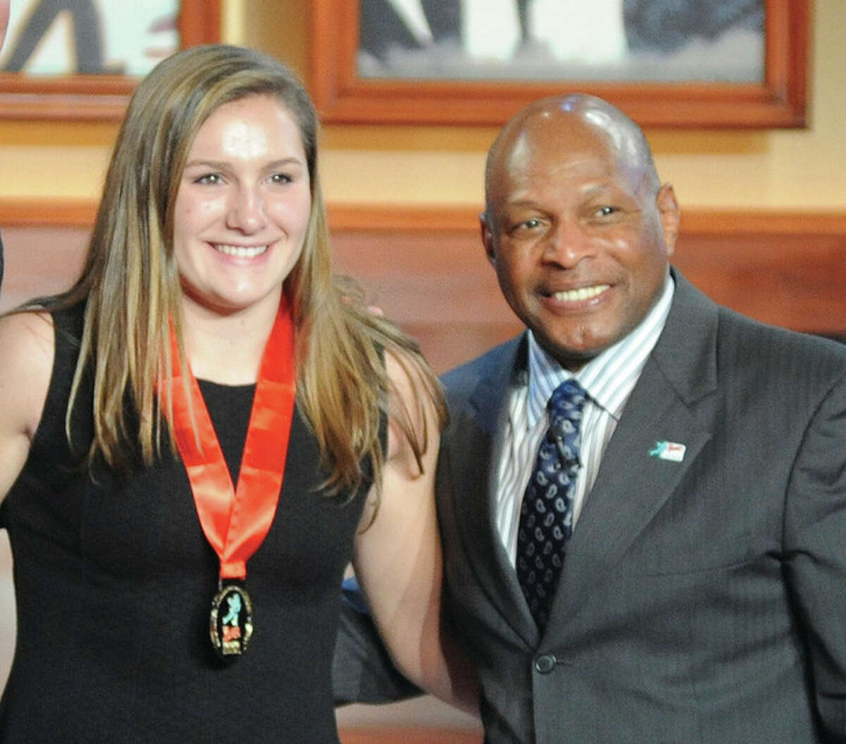 Hour photo/John Nash Wilton High senior Casey Pearsall, left, poses for a photo with two-time Heisman Trophy winner Archie Griffin after she received her medal for being one of 12 national finalists for the Wendy's High School Heisman at the Best Buy Theater in New York City on Friday night.