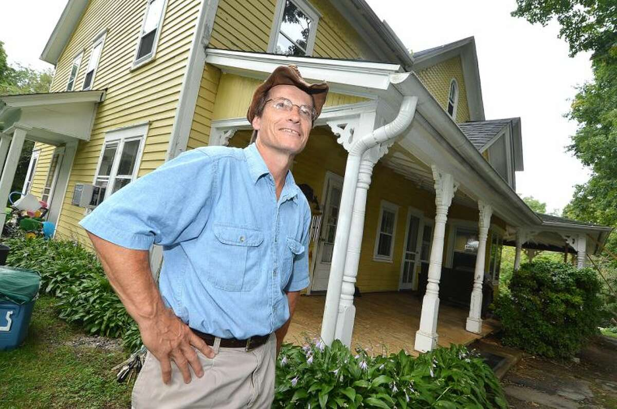 Kevin Meehan stands in front of the Yellow House at Ambler Farm in Wilton.Town officials have signed a pledge to reduce energy use in municipal buildings by 20 percent by the year 2018.