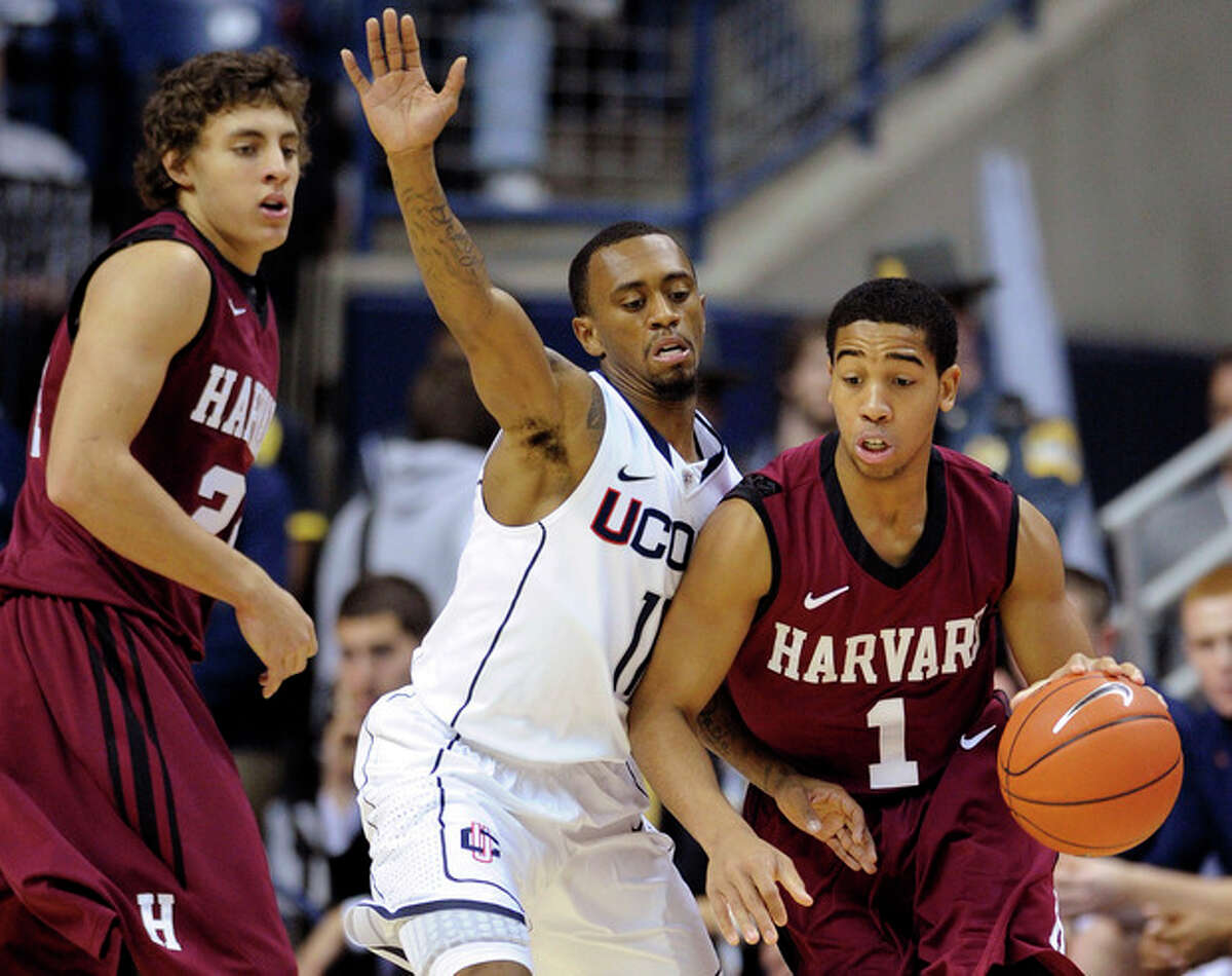 Harvard's Siyani Chambers (1) is defended by Connecticut's Ryan Boatright, center, as Harvard's Jonah Travis, left, looks on during the first half of an NCAA college basketball game in Storrs, Conn., Friday, Dec. 7, 2012. (AP Photo/Fred Beckham)