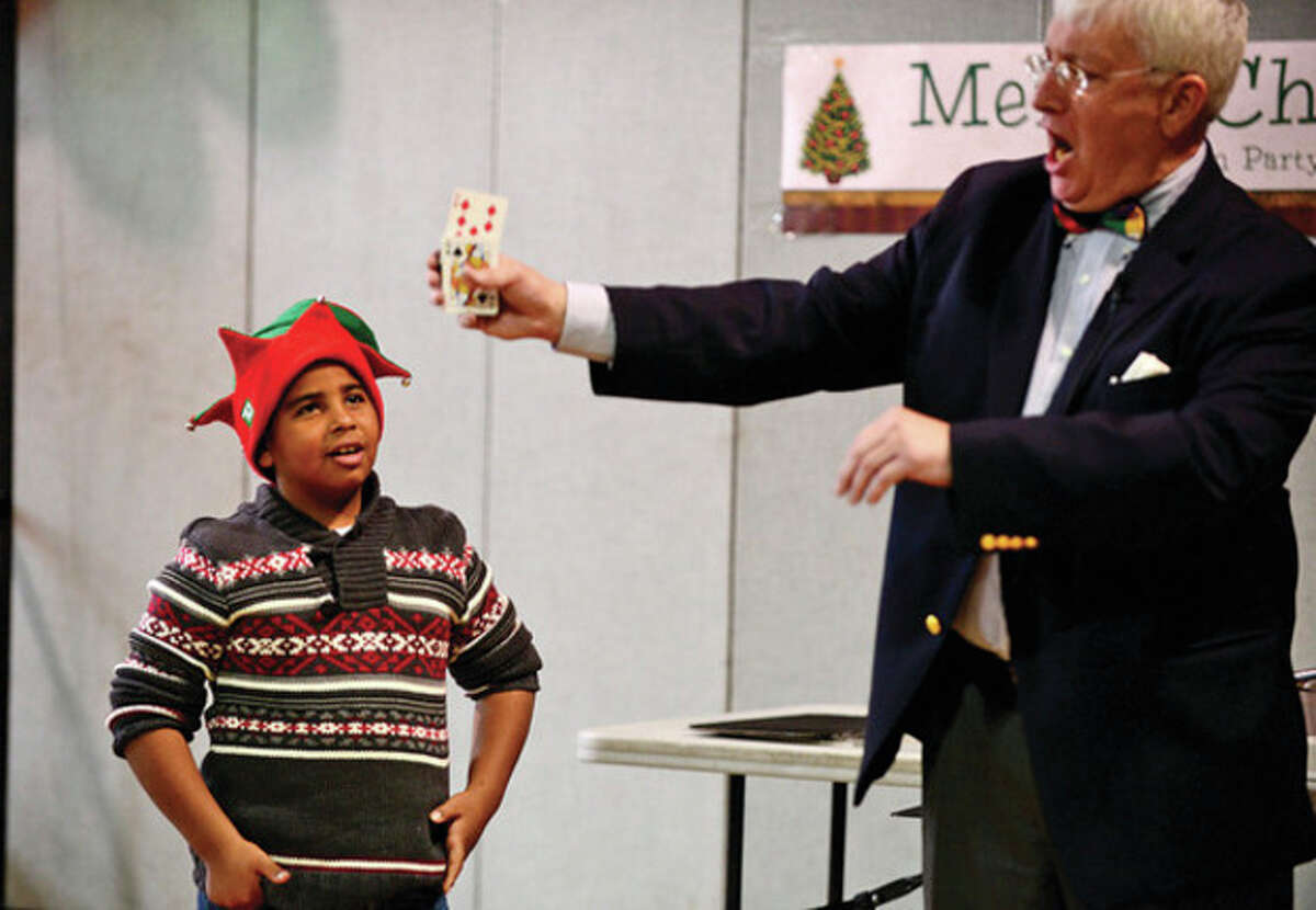 Isaiah Lopez, 7, helps with the magic tricks of Tom O'Brien at the Norwalk Community Police and The Police Athletic League annual Christmas party for under privileged youngsters at Side By Side School Saturday. Hour photo / Erik Trautmann