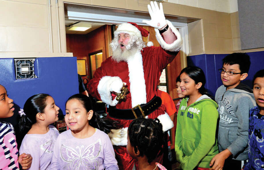 Hour photo / Erik TrautmannRetired police officer Joe Kubik plays Santa at the annual Christmas party for underprivileged youngsters sponsored by Norwalk Community Policing Unit and the Police Athletic League at Side By Side School Saturday. / (C)2012, The Hour Newspapers, all rights reserved