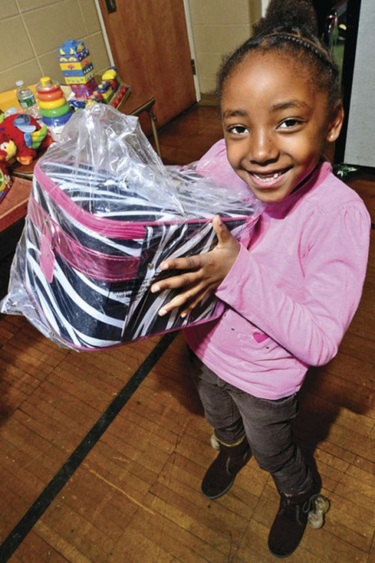 7 year old Trinity Slaughter receives a Christmas gift at the Norwalk Community Police and The Police Athletic League annual Christmas party for under privileged youngsters at Side By Side School Saturday. Hour photo / Erik Trautmann