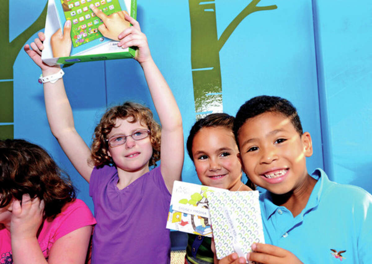 @Cutline Byline:Hour photo / Erik Trautmann Norwalk Office of Early Childhood and the Norwalk Public Library giveaway prizes for children enrolled in summer reading program including Katherine Connors, Sydney Mashia and Cristian Young during a reception Friday