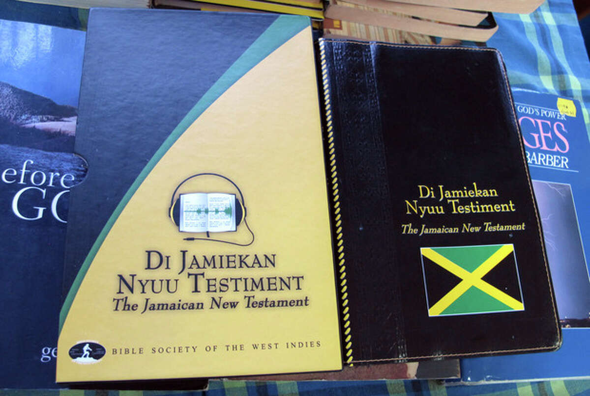 """In this Dec. 3, 2012 photo, the covers of two editions of the new Jamaican patois translation of the New Testament are shown at the office of the Bible Society of the West Indies in Kingston, Jamaica. After years of translation from the original Greek, the Bible Society is releasing in Jamaica print and audio CD versions of the first patois translation of the New Testament, or """"Di Jamiekan Nyuu Testiment."""" The language was created by slaves who were brought to the island by European colonizers, and some say it was designed to prevent slave masters from understanding their words. (AP Photo/David McFadden)"""