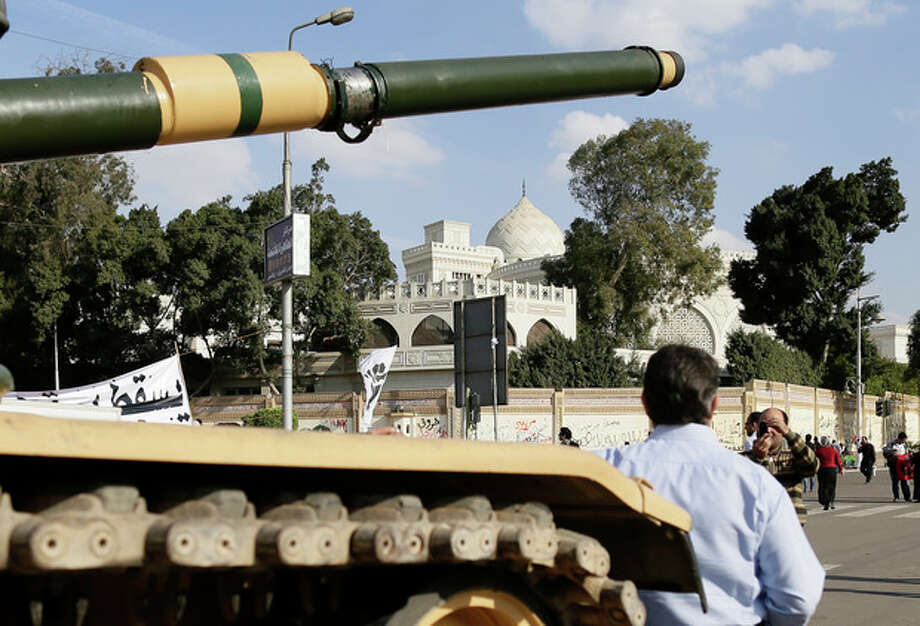 An Egyptian protester takes a picture with his mobile of another in front of an Egyptian army tank outside the presidential palace, background, in Cairo, Egypt, Saturday, Dec. 8, 2012. Egypt's military has warned of 'disastrous consequences' if the political crisis gripping the country is not resolved through dialogue. (AP Photo/Hassan Ammar) / AP
