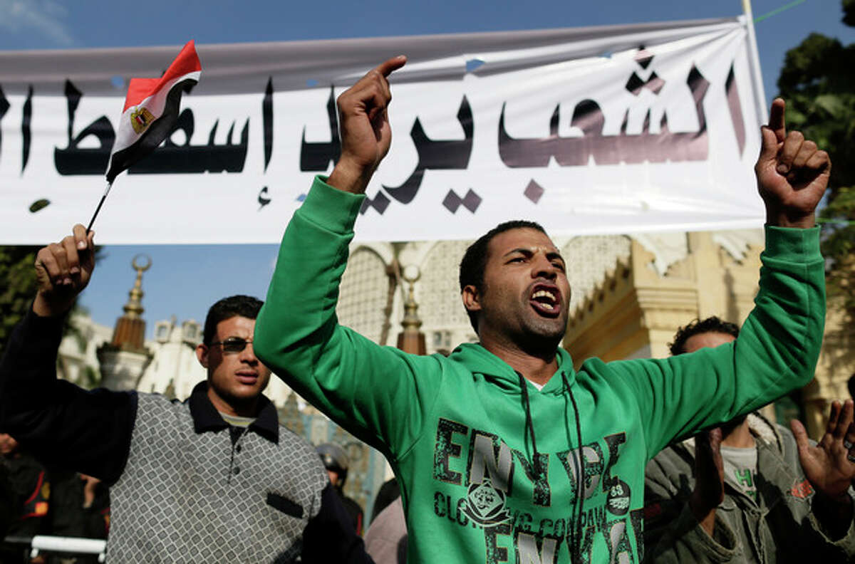 Egyptian protesters chant anti-Muslim Brotherhood and Egyptian President Mohammed Mosri slogans outside the presidential palace under a banner with a defaced picture of President Mohammed Morsi and Arabic that reads