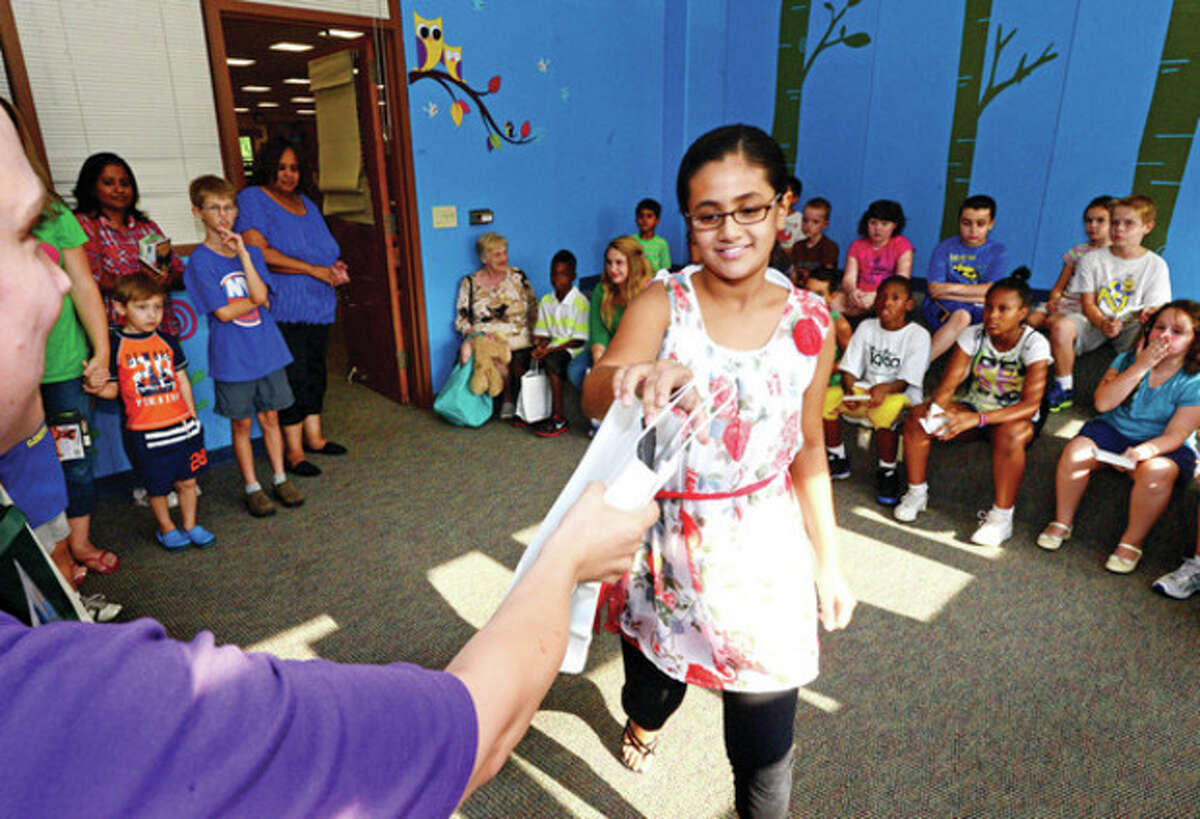 Hour photo / Erik Trautmann Norwalk Office of Early Childhood and the Norwalk Public Library giveaway prizes for children enrolled in summer reading program including 11 year old Saitrisha Gulappa during a reception Friday.