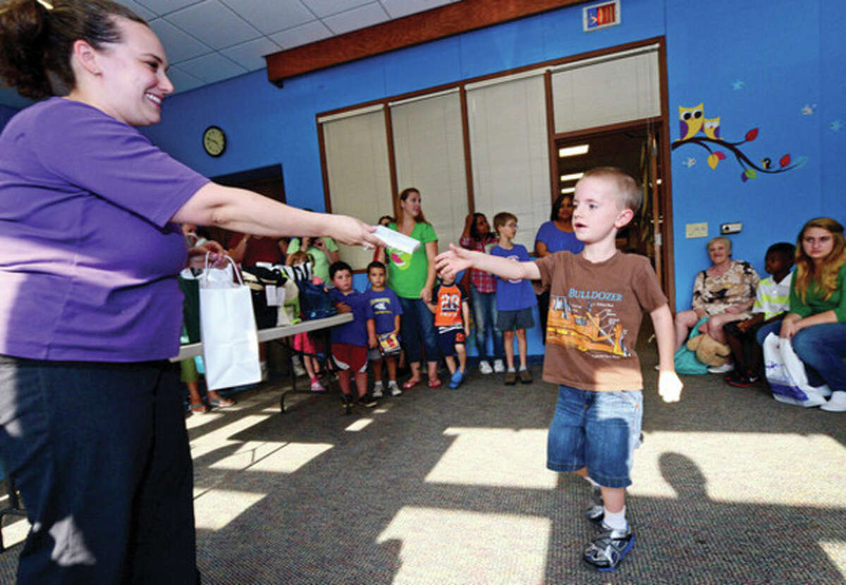 Hour photo / Erik Trautmann Norwalk Office of Early Childhood and the Norwalk Public Library's Vicki Otis gives away prizes for children enrolled in summer reading program including 6 year old Aidan Moon during a reception Friday.