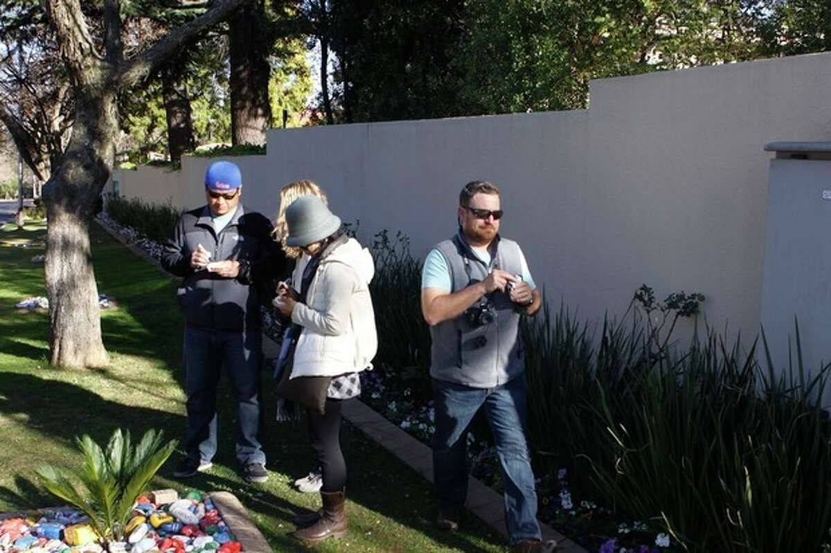 Tourists write get well messages on pebbles for former president Nelson Mandela to place them in a garden outside his Johannesburg home Saturday, Aug. 31, 2013. The South African government issued a statement that Mandela remains hospitalized in a