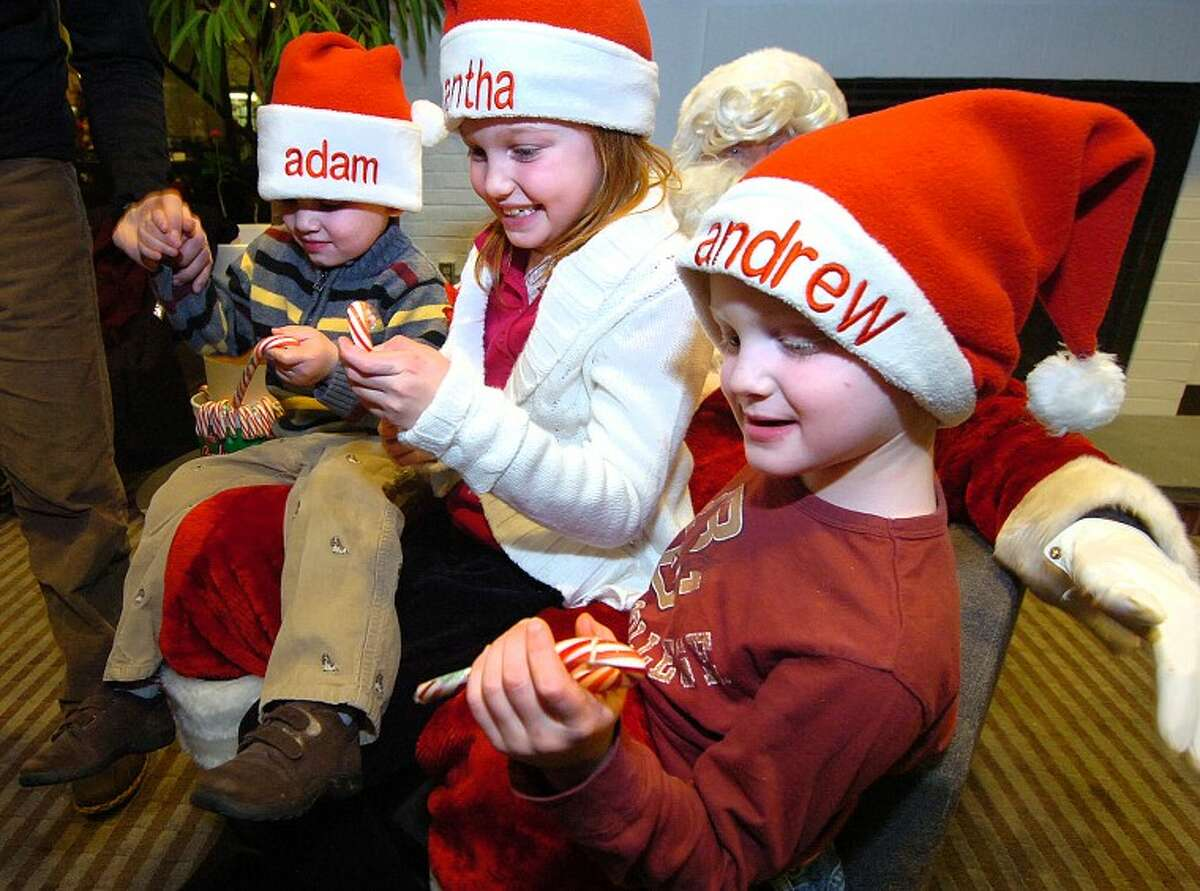 Hour Photo/Alex von Kleydorff. Adam Mims Samantha Mims and Andrew Mims all get Candy Canes from Santa during the Wilton Holiday walk