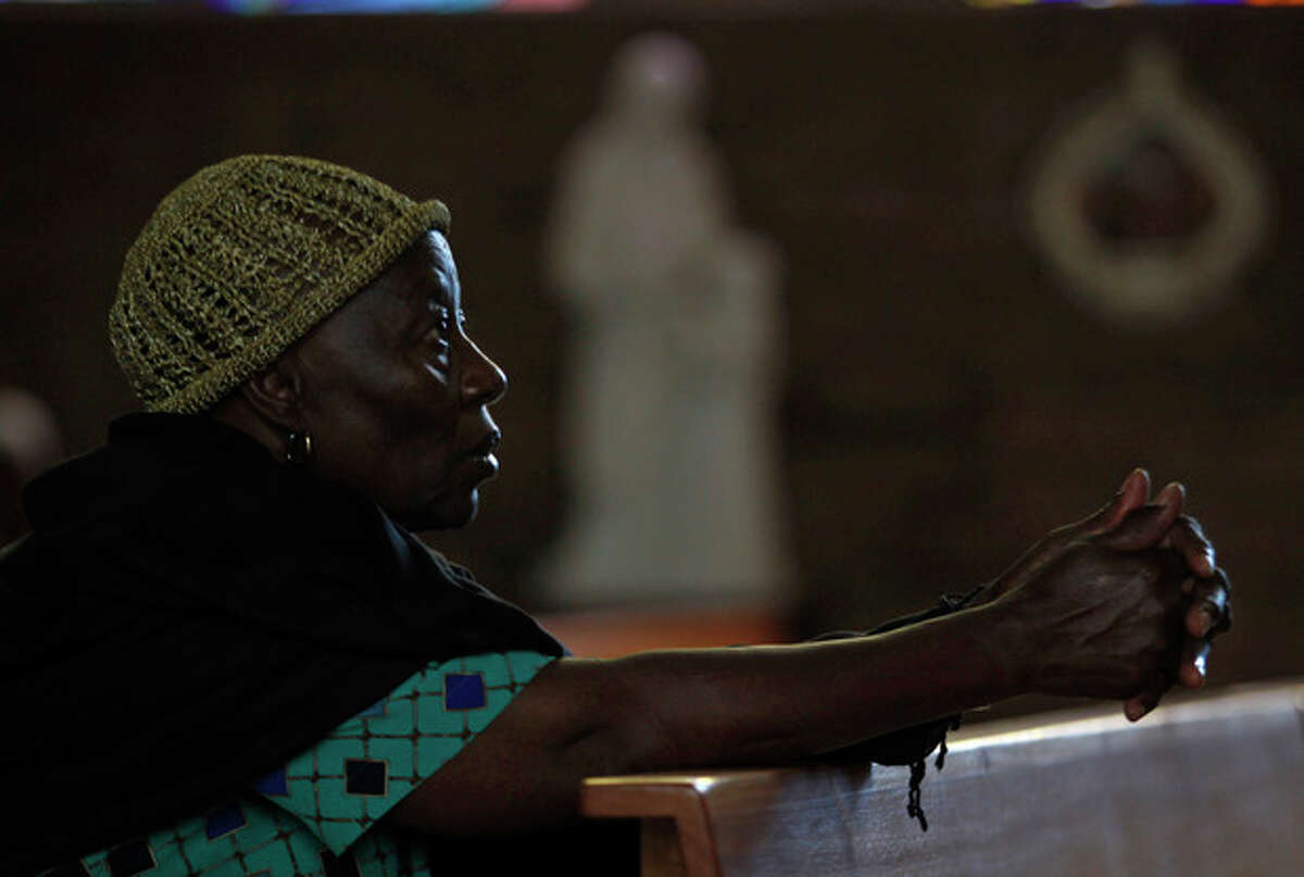 A worshipper prays at the Regina Mundi Church in Soweto, South Africa, prior to early morning Mass, Tuesday, Dec 11 2012. Calls for prayer have been made for former president Nelson Mandela who was admitted to the 1 Military Hospital in Pretoria at the weekend. South Africa's presidency says former President Nelson Mandela is suffering from a recurring lung infection and is responding to treatment. The statement Tuesday, Dec. from presidential spokesman Mac Maharaj said the 94-year-old anti-apartheid icon is