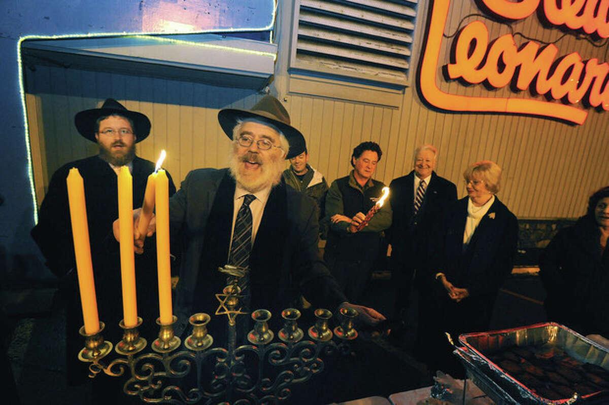 Hour photo/ Matthew Vinci Rabbi Yehoshua Hecht of Beth Israel Synagogue of Westport/Norwalk lights the menorah Monday at the annual celebration held at Stew Leonard's.