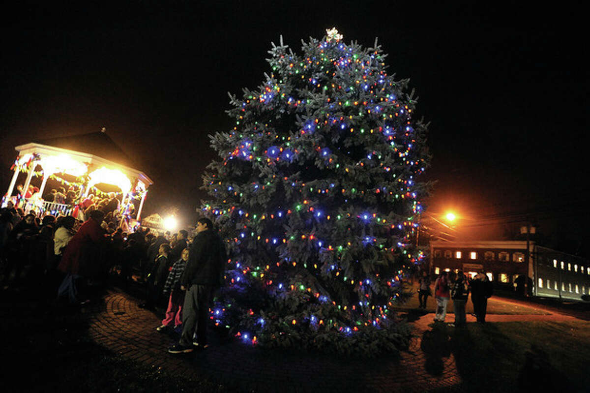 Hour photo/Matthew Vinci A crowd gathers to admire the tree on the Norwalk Green at the annual Christmas tree lighting on Monday night.