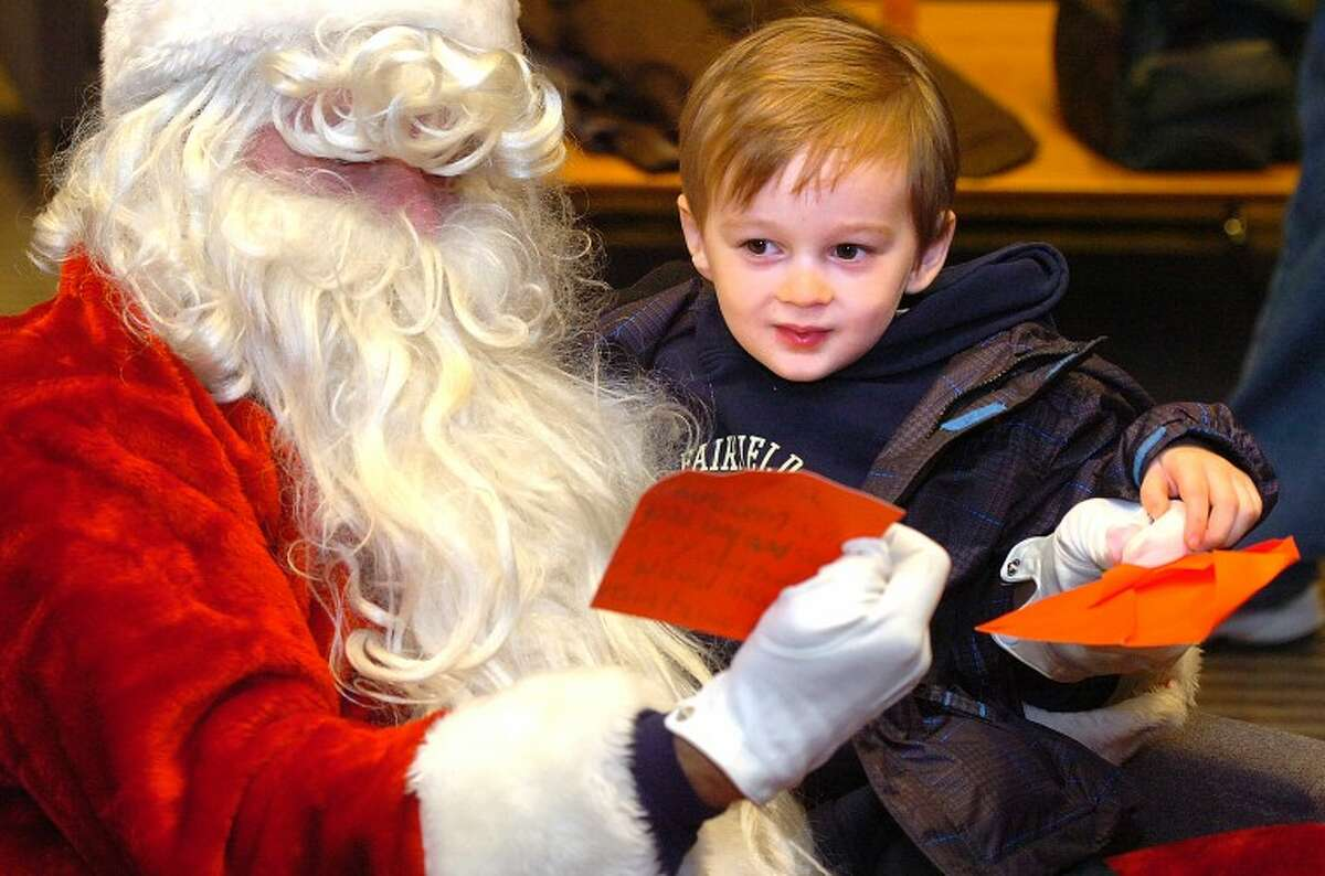 Hour Photo/Alex von Kleydorff. 3yr old Rocco Equale hands a letter to Santa at the Wilton Holiday walk