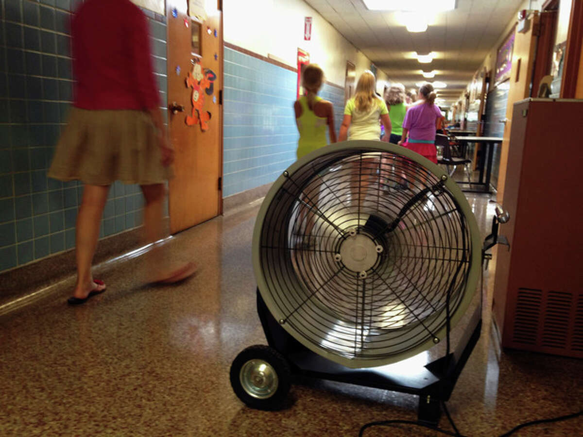 In this Wednesday, Aug. 28, 2013 photo, a teacher and students at Washington Elementary School in Monticello, Ill., walk past a large fan used to help cool the school. The school, built in 1894, has air conditioning in only a few spots and has been sending students home early this new school year as temperatures push into the 90s every day. (AP Photo/David Mercer)