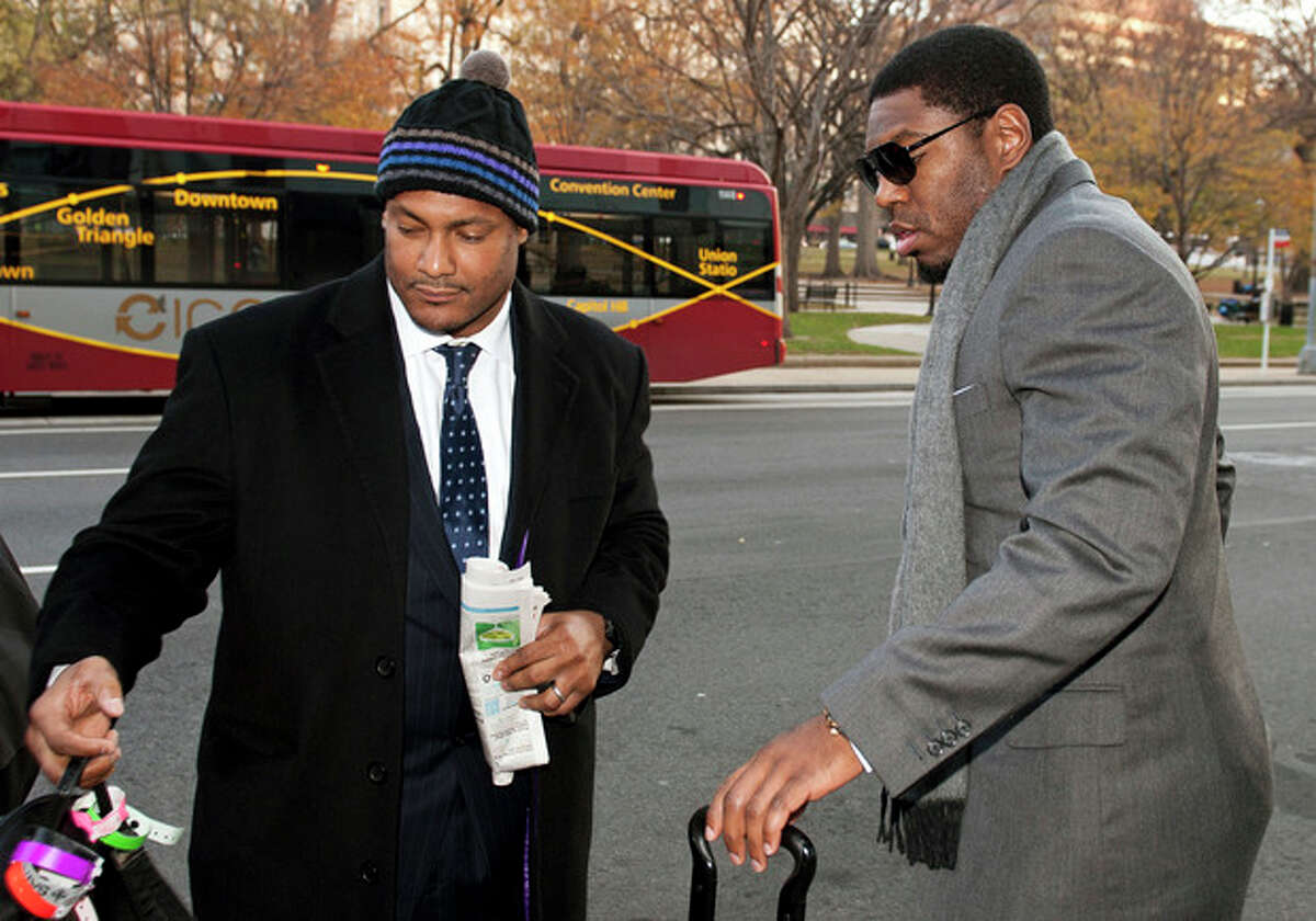 FILE - In this Nov. 30, 2012, file photo, New Orleans Saints football defensive end Will Smith, left, and linebacker Jonathan Vilma arrive at an attorney's office in Washington, for a hearing on their appeals of bounties suspensions. Former Commissioner Paul Tagliabue, who was appointed to handle a second round of player appeals to the league, has informed all parties he planned to rule by Tuesday, Dec. 11, and his decision could affect whether two current Saints ?- Jonathan Vilma and Will Smith ?- get to play out the season. (AP Photo/Cliff Owen, File)