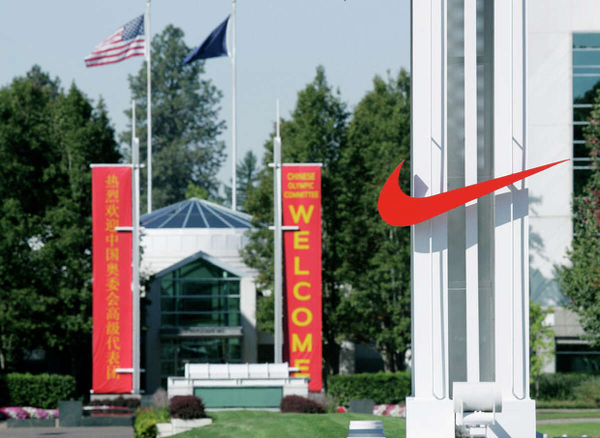 FILE - In this Sept. 29, 2006 file photo, the red Nike swoosh marks the entrance to the company's headquarters campus in Beaverton, Ore. Nike wants to expand its Oregon operations and hire as many as 12,000 new workers by 2020 but wants the government to promise it won't change the state tax code. Oregon Gov. John Kitzhaber says he'll call the Legislature into session Friday to create a law to give Nike its promise. (AP Photo/Don Ryan, File)