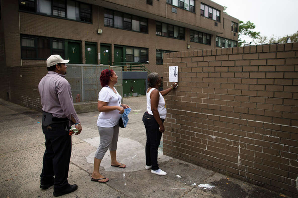 Pedestrians look at a flyer bearing an image of Antiq Hennis, the 1-year-old boy who was shot in his stroller during a walk with his parents a day earlier, that is posted on a wall outside an apartment complex, Monday, Sept. 2, 2013, in the Brownsville neighborhood in the Brooklyn borough of New York. New York Police Department investigators believe the boy's father may have been the intended target and are pursuing leads. (AP Photo/John Minchillo)