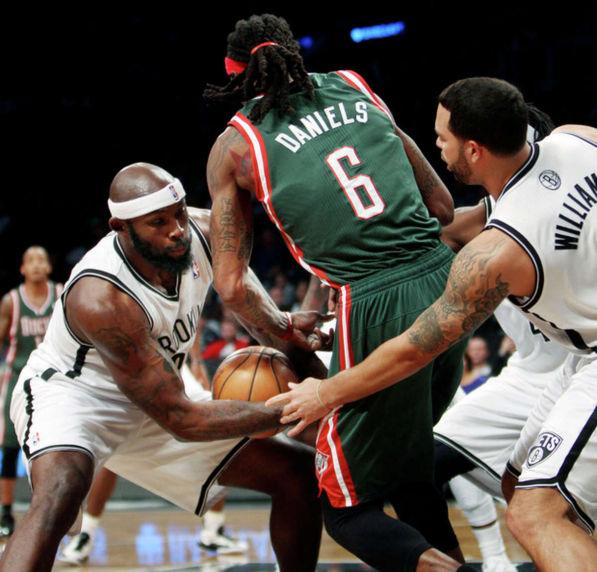 Brooklyn Nets' Reggie Evans, left, steals the ball from Milwaukee Bucks' Marquis Daniels, center, as Nets' Deron Williams helps during the first half of an NBA basketball game at Barclays Center, Sunday, Dec. 9, 2012, in New York. (AP Photo/Seth Wenig)