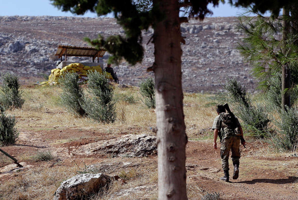 A Turkish soldier patrols at the Cilvegozu gate border with Syria, Monday, Sept. 2, 2013. U.S. President Barack Obama is inviting former foe Sen. John McCain to the White House, hoping one of Congress' most intractable foreign policy hawks will help sell the idea of a U.S. military intervention in Syria to a nation deeply scarred by more than a decade of war. (AP Photo/Gregorio Borgia)