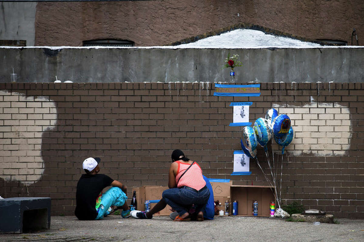 Mourners visit a memorial for Antiq Hennis, in the Brownsville neighborhood in the Brooklyn borough of New York, Monday, Sept. 2, 2013, where a day earlier, the 1-year-old boy was shot and killed in his stroller during a walk with his parents. New York Police Department investigators believe the boy's father may have been the intended target and are pursuing leads. (AP Photo/John Minchillo)