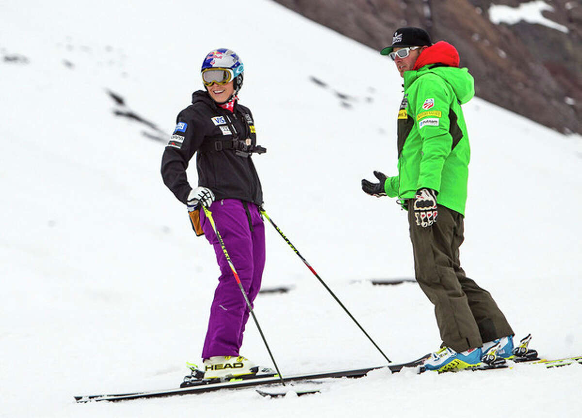 In this Aug. 31, 2013 photo provided by Red Bull, Lindsey Vonn, left, works with U.S. ski team coach Jeff Fergus in Portillo, Chile. The four-time World Cup overall champion returned to the slopes over the weekend nearly seven months after her injury. She eased her way back with two gentle and relaxed training runs. (AP Photo/Red Bull, Jonathan Selkowitz)