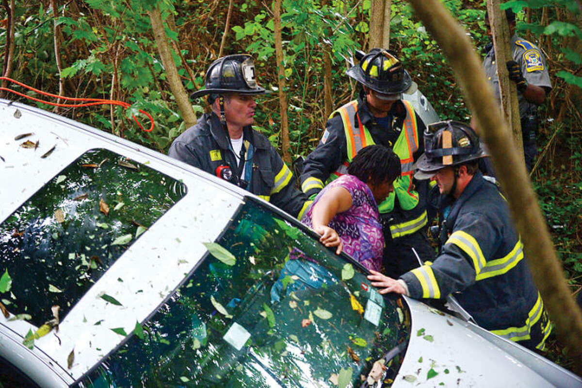 The driver of a BMW that crashed through a protective barrier and plunged over 30 ft. into a storm culvert is evacuated following a one car accident on the Merritt Parkway Southbound near exit 40 in Norwalk Tuesday morning. Hour photo / Erik Trautmann