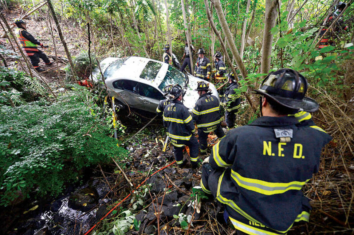 A BMW crashed through a protective barrier and plunged over 30 ft. into a storm culvert during a one car accident on the Merritt Parkway Southbound near exit 40 in Norwalk Tuesday morning. Hour photo / Erik Trautmann