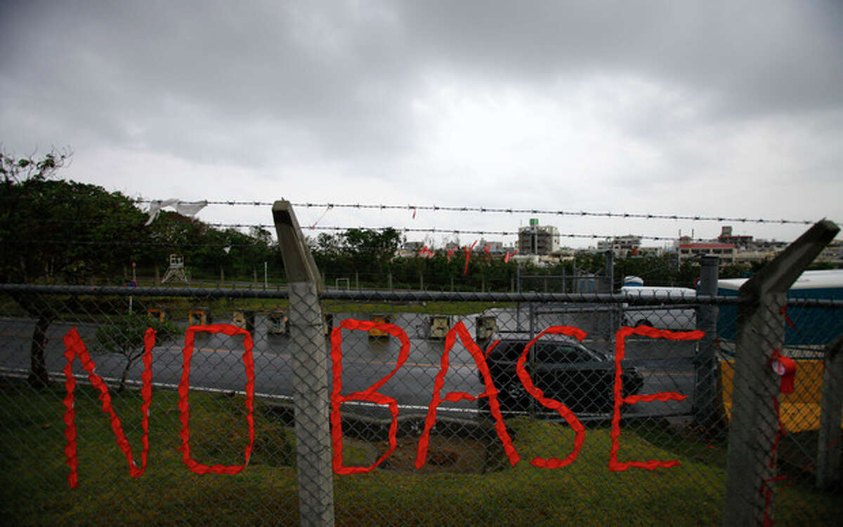 In this Friday, Nov. 30, 2012 photo, a slogan against the base is displayed on the fence enclosed U.S. Marine Corps Futenma Air Station in Ginowan, Okinawa, southwestern Japan. Okinawans are angry that Japan approved the deployment of 12 Osprey aircraft, which began in October, though the government has asked for additional assurances of the aircraft's safety. Washington said the Osprey is safe and is needed to ensure regional security. (AP Photo/Junji Kurokawa)
