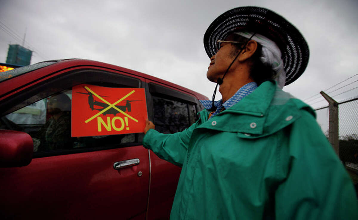 In this Friday, Nov. 30, 2012 photo, a local protester flashes an anti-Osprey placard to a window of a car driven by a member of the U.S. military at a gate of the U.S. Marine Corps Futenma Air Station in Ginowan, Okinawa, southwestern Japan. Okinawans are angry that Japan approved the deployment of 12 Osprey aircraft, which began in October, though the government has asked for additional assurances of the aircraft's safety. Washington said the Osprey is safe and is needed to ensure regional security. (AP Photo/Junji Kurokawa)