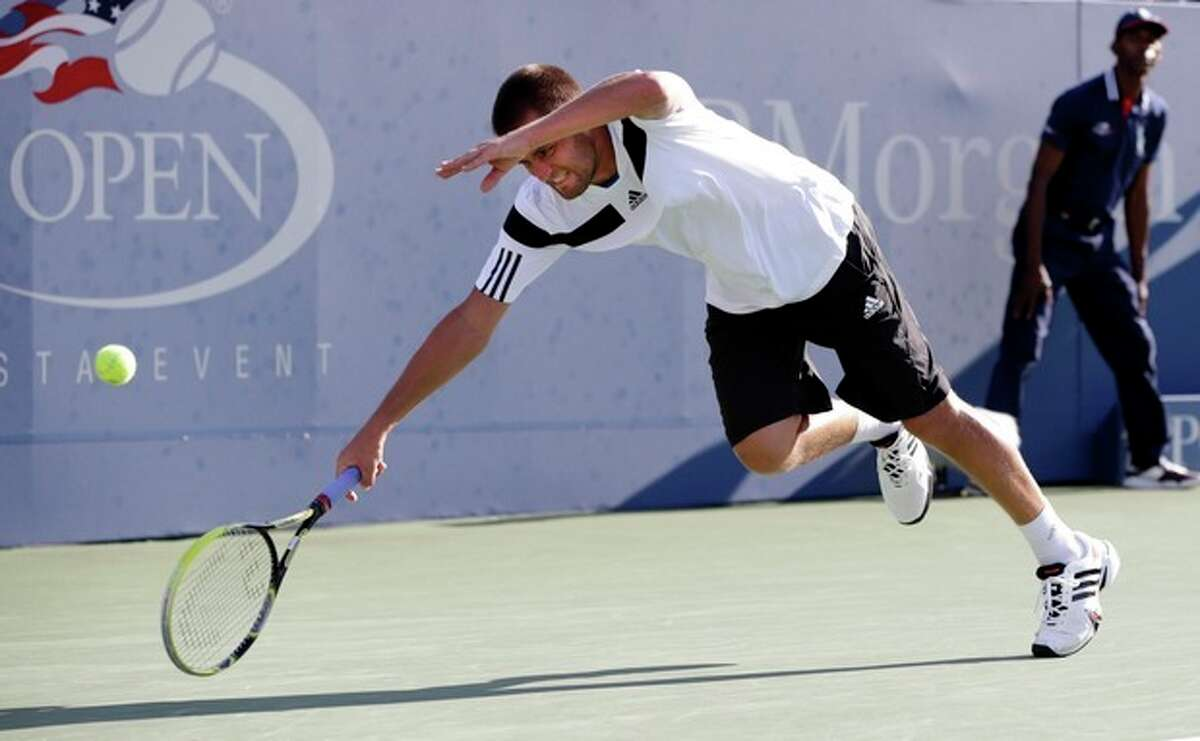 Mikhail Youzhny, of Russia, loses his balance chasing down a shot from Lleyton Hewitt, of Australia, during the fourth round of the 2013 U.S. Open tennis tournament, Tuesday, Sept. 3, 2013, in New York. (AP Photo/Kathy Willens)