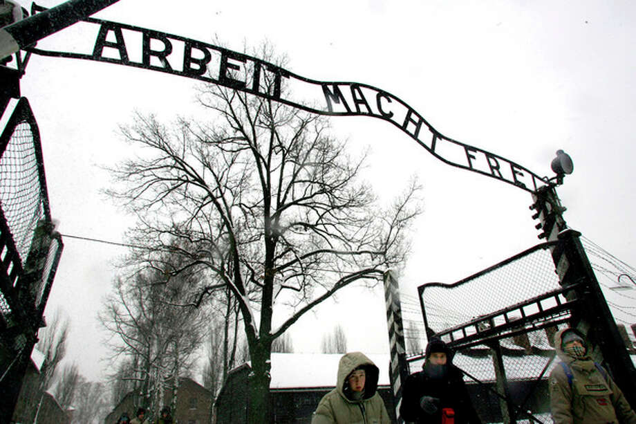 "FILE --In a Jan. 26, 2005 file photo, visitors walk under the notorious ""Arbeit Macht Frei"" sign at the entrance gate of the Auschwitz Nazi concentration camp in Oswiecim, southern Poland. The special prosecutors' office that investigates Nazi war crimes said Tuesday Sept. 3, 2013 it is recommending charges against dozens of alleged former Auschwitz guards, opening the possibility of a new wave of trials almost 70 years after the end of World War II. Kurt Schrimm, the head of the Ludwigsburg federal prosecutors' office, said an investigation of about 50 alleged former guards turned up enough evidence to recommend that state prosecutors pursue charges of accessory to murder against 30 of them in Germany. (AP Photo/Herbert Knosowski/file) / AP2005"