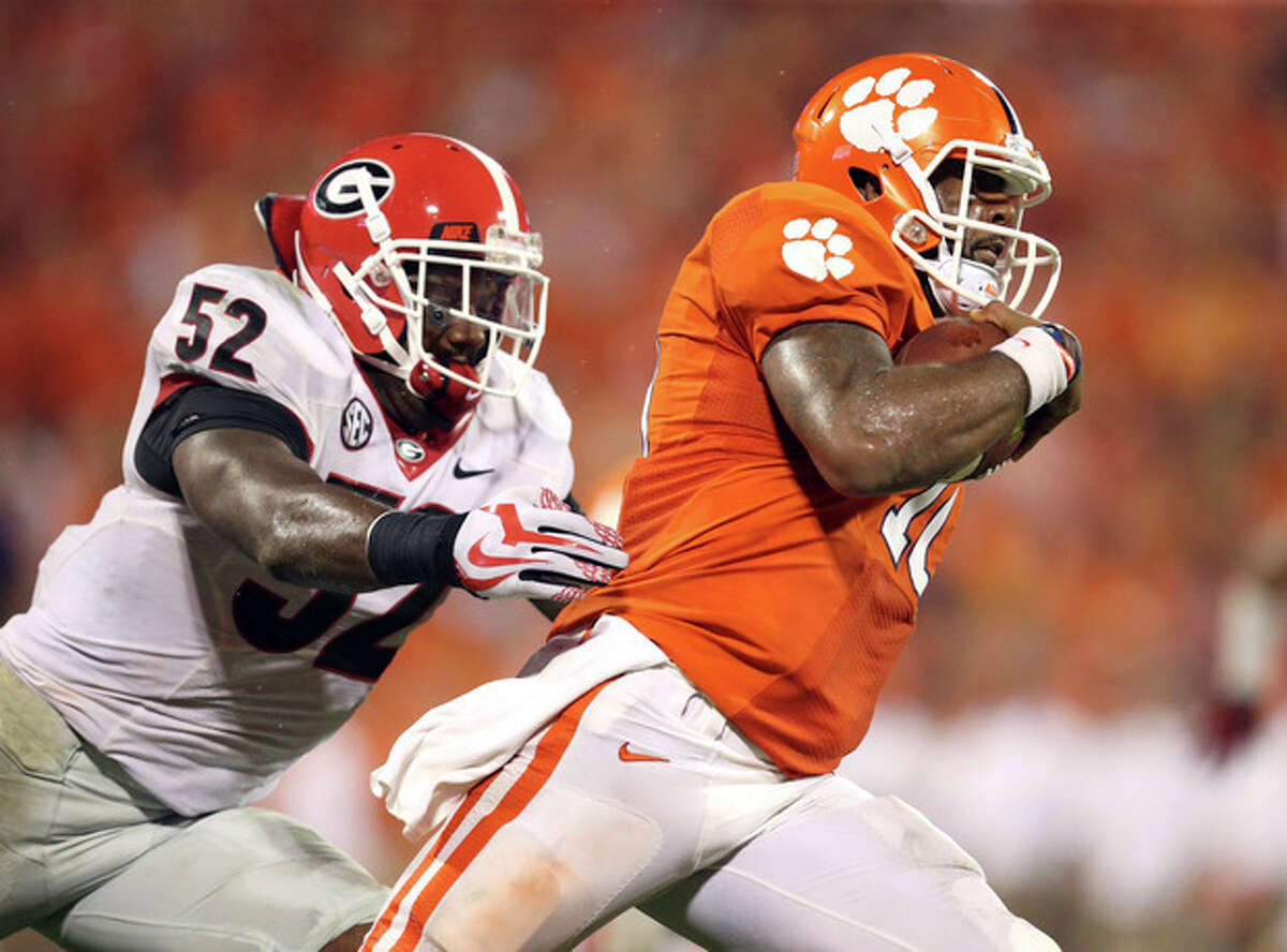 Clemson quarterback Tajh Boyd, right, outruns the tackle of Georgia linebacker Amarlo Herrera, left, in the second half of their NCAA college football game at Memorial Stadium, Saturday, Aug. 31, 2013, in Clemson, SC. Clemson defeated Georgia 38-35. (AP Photo/Atlanta Journal-Constitution, Jason Getz) MARIETTA DAILY OUT; GWINNETT DAILY POST OUT; LOCAL TV OUT; WXIA-TV OUT; WGCL-TV OUT.