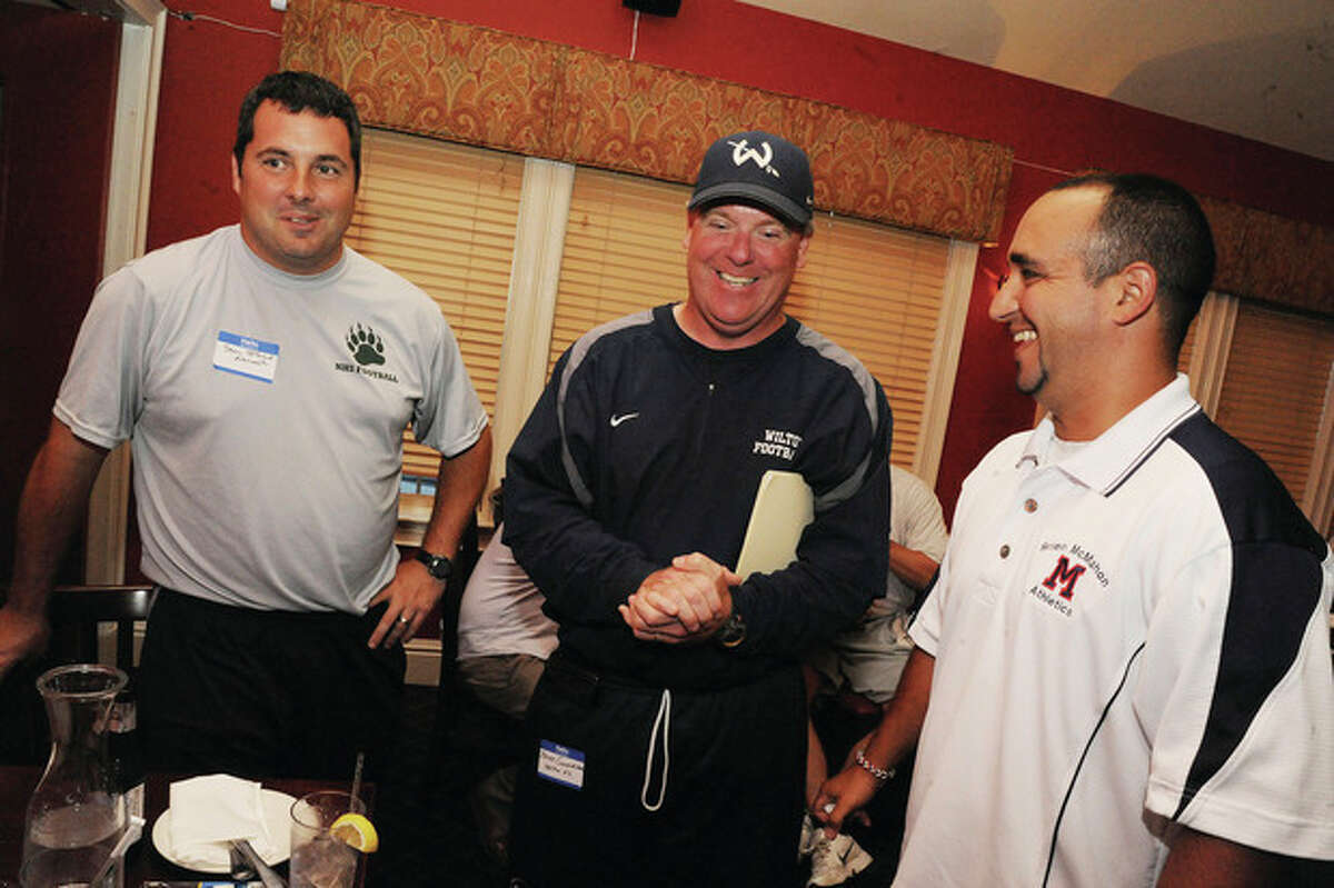 Hour photo/Matthew Vinci Coaches, from left, Sean Ireland of Norwalk High, Bruce Cunningham of Wilton and Brien McMahon's AJ Albano share a laugh during Tuesday night's FCIAC football media gathering in Stamford.
