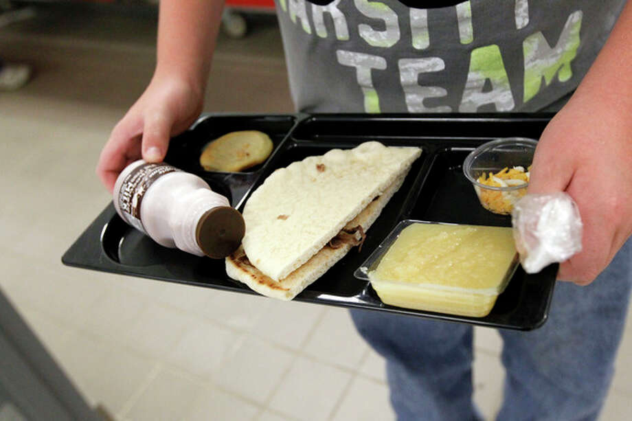 FILE - In this Wednesday, Sept. 12, 2012 file photo, a student at Eastside Elementary School in Clinton, Miss., holds a school lunch served under federal standards, consisting of a flatbread roast beef sandwich, apple sauce, chocolate milk and a cookie. After just one year, some schools across the nation are dropping out of what was touted as a healthier federal lunch program, complaining that so many students refused the meals packed with whole grains, fruits and vegetables that their cafeterias were losing money. (AP Photo/Rogelio V. Solis, File) / AP