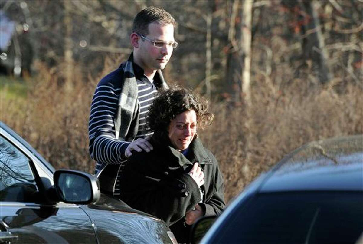 A man and woman leave the staging area for family around near the scene of a shooting at the Sandy Hook Elementary School in Newtown, Conn., about 60 miles (96 kilometers) northeast of New York City, Friday, Dec. 14, 2012. An official with knowledge of Friday's shooting said 27 people were dead, including 18 children. (AP Photo/Jessica Hill)