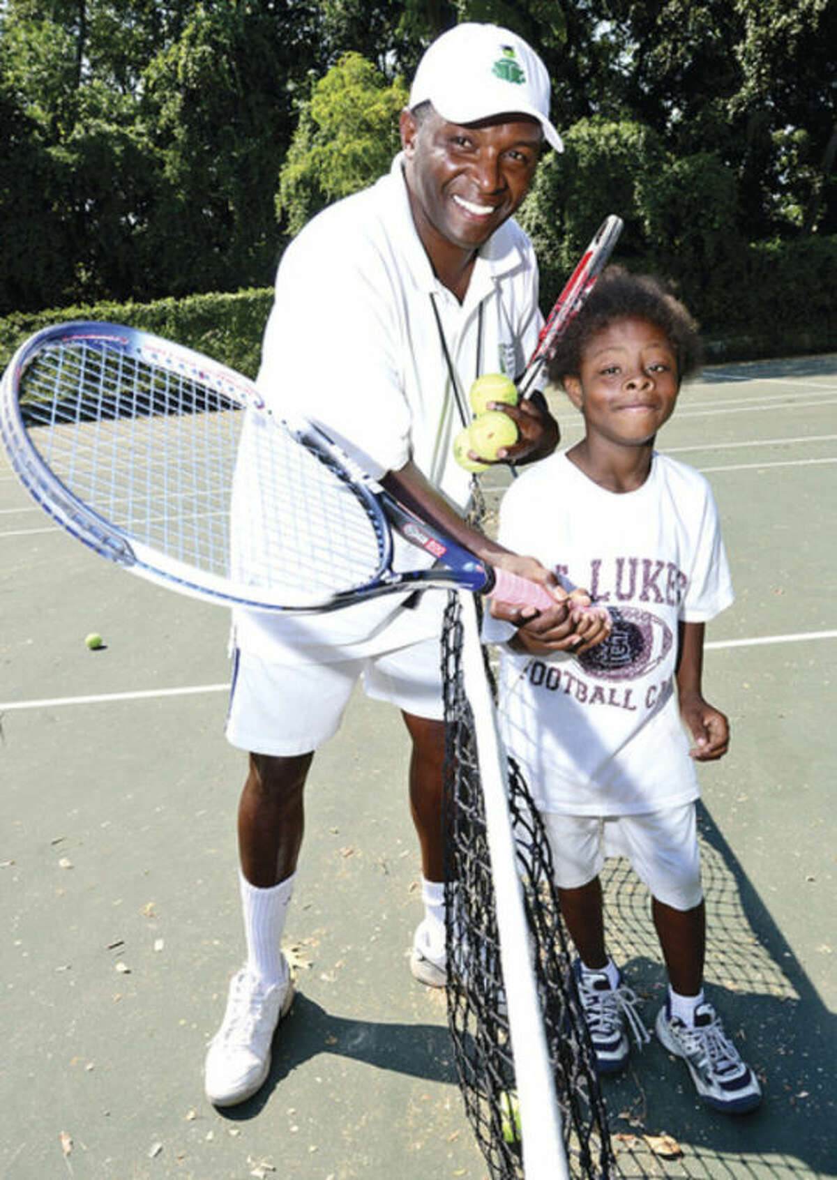 David Kimani, director of tennis for the Norwalk Grassroots Tennis program, gives a few pointers to 10-year-old Johnny Slade at Springwood Park behind Roodner Court. @Cutline Byline:Hour photo/ Erik Trautmann
