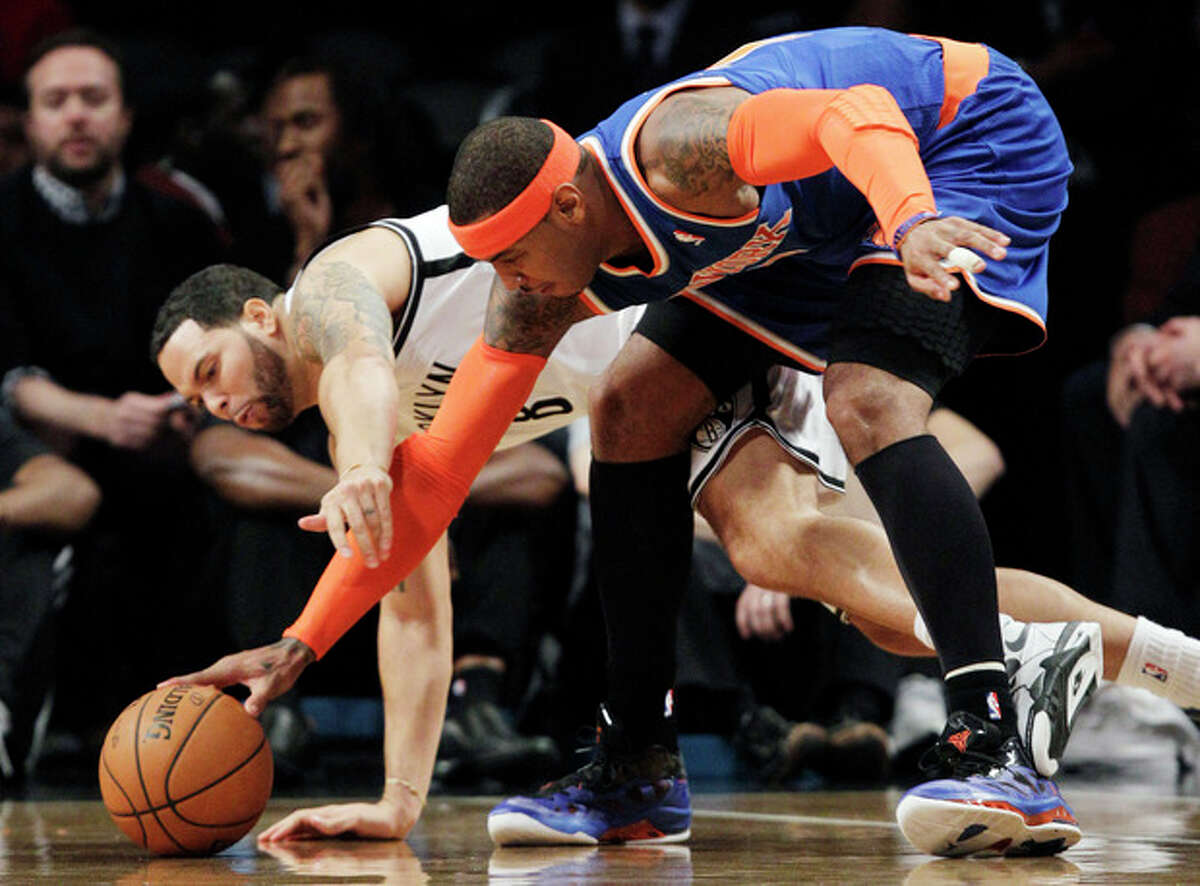 Brooklyn Nets guard Deron Williams (8) trips over the legs of New York Knicks forward Carmelo Anthony (7) as they compete for a loose ball in the first half of their NBA basketball game at Barclays Center, Tuesday, Dec. 11, 2012, in New York. (AP Photo/Kathy Willens)