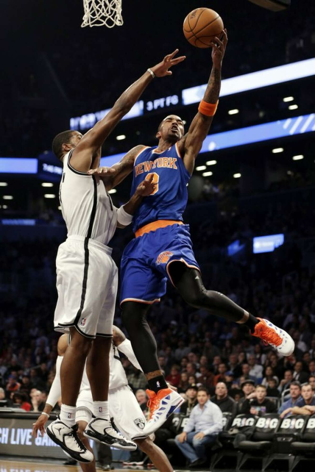 New York Knicks guard J.R. Smith (8) shoots as Brooklyn Nets guard Joe Johnson (7) defends in the first half of their NBA basketball game at Barclays Center, Tuesday, Dec. 11, 2012, in New York. (AP Photo/Kathy Willens)