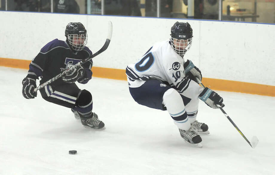 Hour photo/John NashWilton's Josh Worley, right, and Tri-Town's Kevin White reverse direction to play the puck during Wednesday's season-opening game at the Winter Garden Ice Arena in Ridgefield. The Warriors skated to a 4-2 victory.