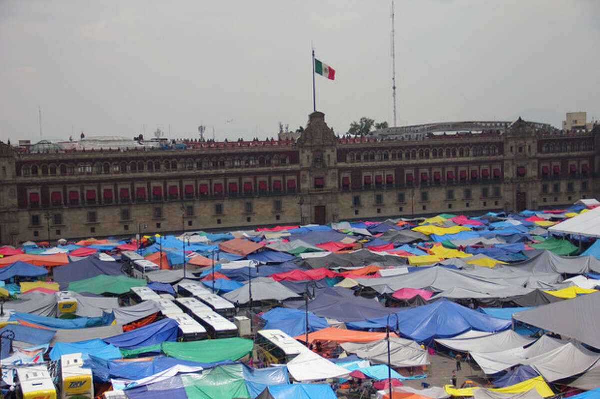 A patchwork of tent tops are spread across Mexico City's main plaza, the Zocalo, where protesting teachers have erected a vast tent encampment, Friday Aug. 23, 2013. Thousands of striking teachers strangled traffic and also blocked access to Mexico City's international airport on Friday, flexing their muscles in a bid to block educational reforms intended to introduce teacher evaluations and reduce union power over hiring decisions. (AP Photo/Gabriela Sanchez)
