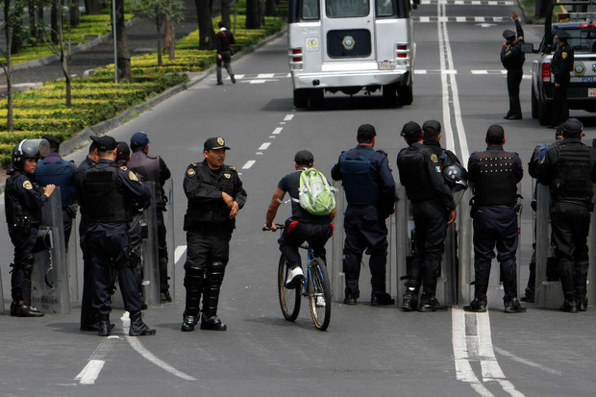 A cyclist rides past police lined up along a main road near Los Pinos presidential residence during protests by teachers in Mexico City, Wednesday, Aug. 28, 2013. Educators protesting a government reform program have in the span of a week disrupted international air travel, forced the cancellation of two major soccer matches, rerouted the planned route of the marathon and snarled already traffic-choked freeways. (AP Photo/Marco Ugarte)