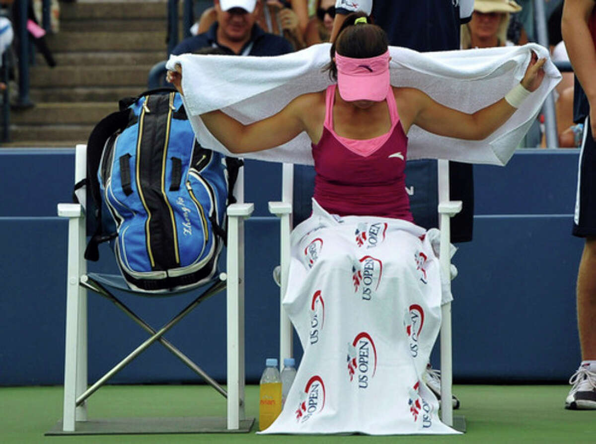Jie Zheng, of China, covers herself with a towel during a rain delay of her second round match against Venus Williams during the 2013 U.S. Open tennis tournament, Wednesday, Aug. 28, 2013, in New York. (AP Photo/Kathy Kmonicek)