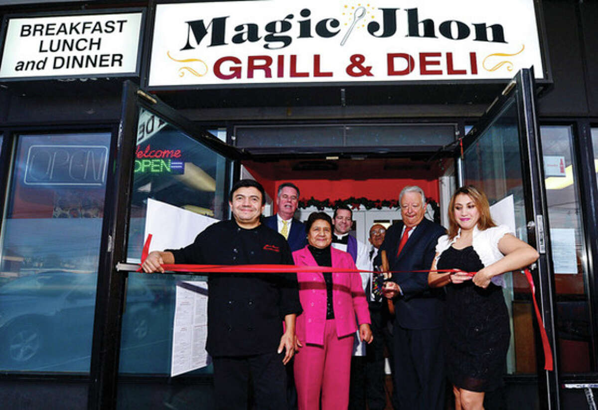 Jhon Guerra, Chamber of Commerce president Ed Musante, Laura Berrones, Father Greg Markey, Mayor Richard Moccia, Gani Berrera and Fanny Guerra cut the ribbon at the grand opening of Magic Jhon Deli on Fort Point St. Tuesday. Hour photo / Erik Trautmann