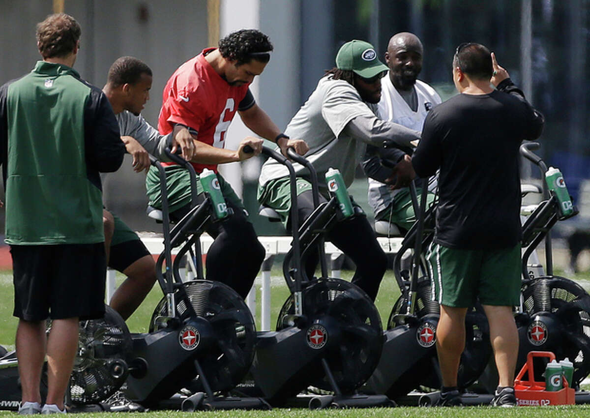 New York Jets quarterback Mark Sanchez, center left, sits on a stationary bike next to cornerback Antonio Cromartie, center right, and wide receiver Santonio Holmes, second from right, during NFL football training camp, Tuesday, Aug. 27, 2013, in Florham Park, N.J.(AP Photo/Julio Cortez)