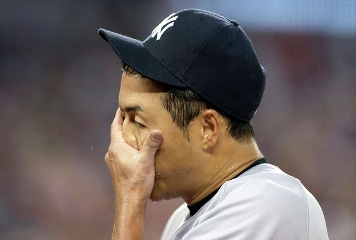 New York Yankees starting pitcher Hiiroki Kuroda, of Japan, wipes his face as he walks off the field following the fourth inning of a baseball game against the Toronto BLue Jays in Toronto on Wednesday, Aug. 28, 2013. (AP Photo/The Canadian Press, Frank Gunn)