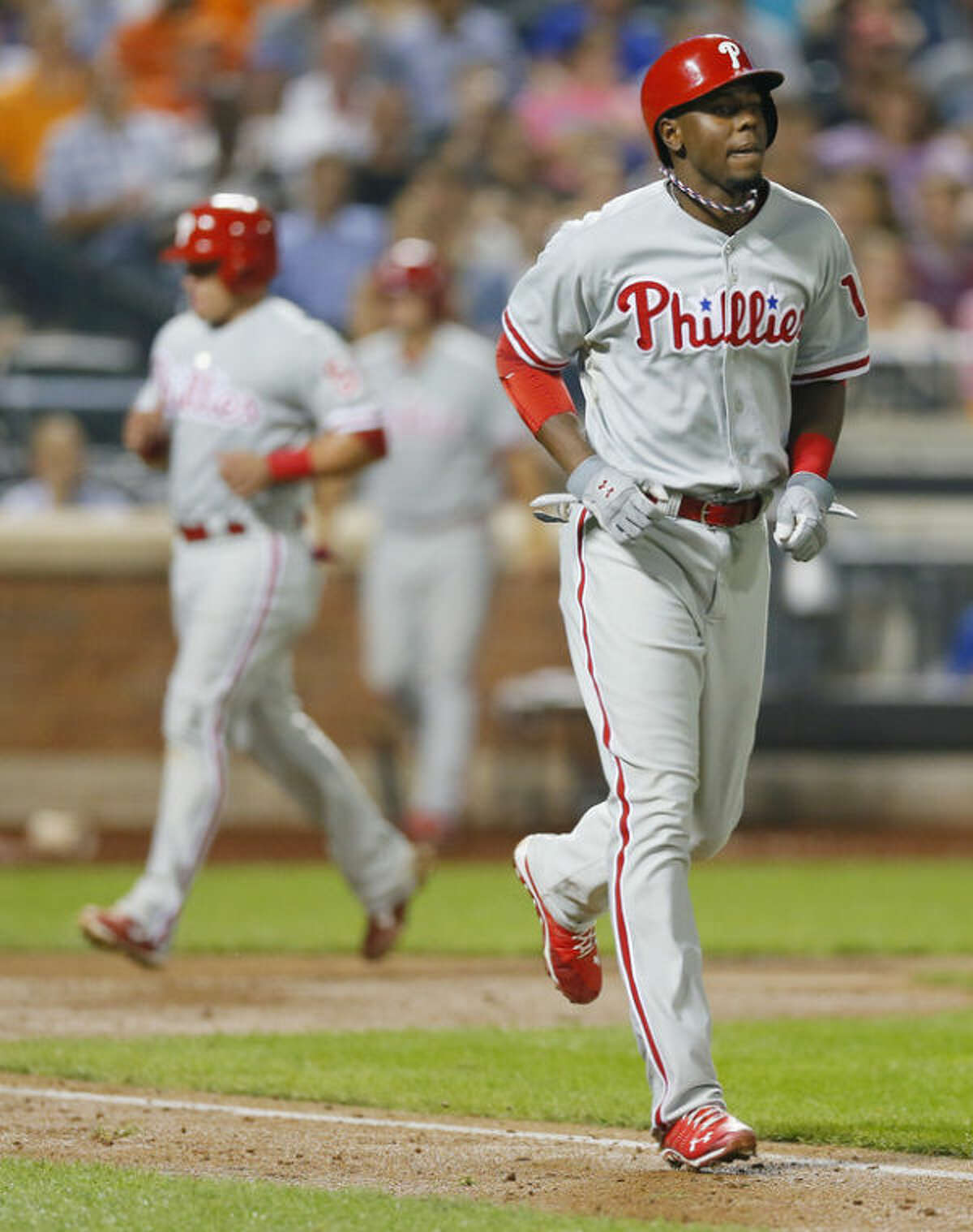 Philadelphia Phillies' John Mayberry Jr. walks to first base after being hit by a pitch with the bases loaded by New York Mets starting pitcher Daisuke Matsuzaka (16) as Phillies' Carlos Ruiz trots home with a run in the background in the fifth inning of a baseball game at Citi Field in New York, Wednesday, Aug. 28, 2013. (AP Photo/Paul J. Bereswill)